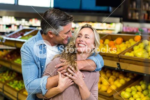 Smiling couple hugging in fruit aisle