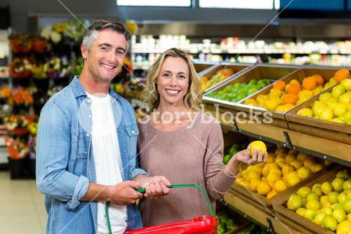 Happy smiling couple picking lemon