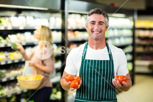 Smiling worker holding vegetables