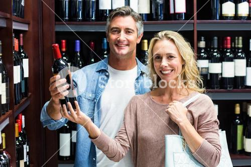 Smiling couple with bottle of wine