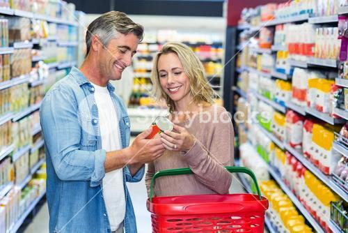 Smiling couple holding canned food