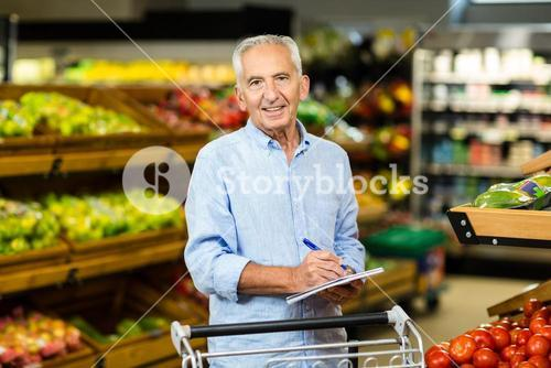 Smiling senior man with grocery list