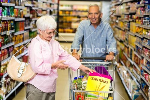 Senior woman taking a box corn flakes