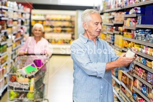 Senior man looking at canned food