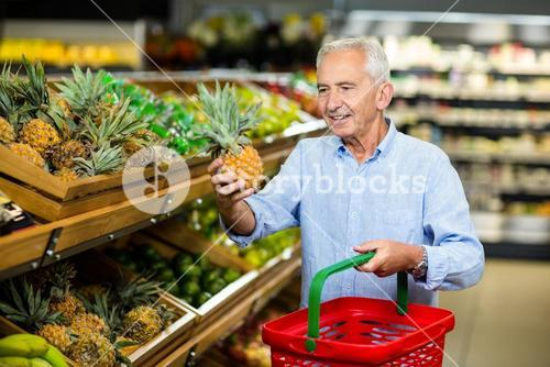 Smiling senior man picking pineapple