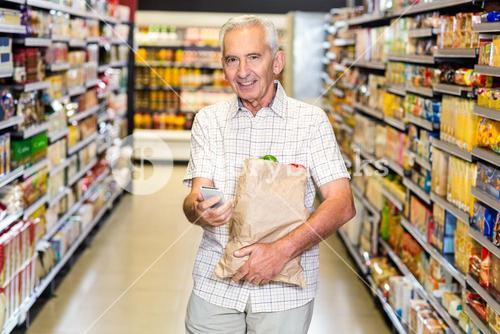 Senior man with grocery bag using smartphone