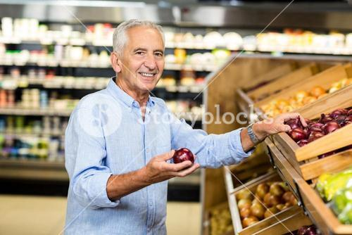 Smiling senior man holding red onion
