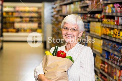 Portrait of smiling senior woman with grocery bag