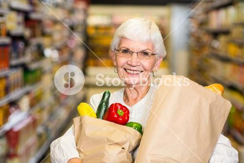 Portrait of smiling senior woman with grocery bags