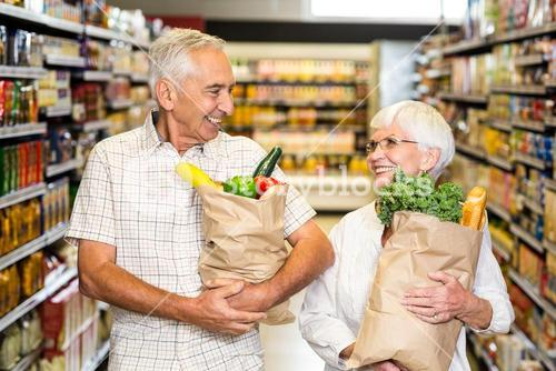 Smiling senior couple holding grocery bags