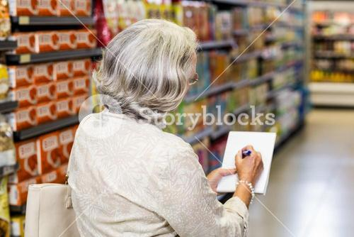 Senior woman checking list at the supermarket