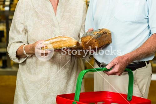 Mid section of senior couple buying bread
