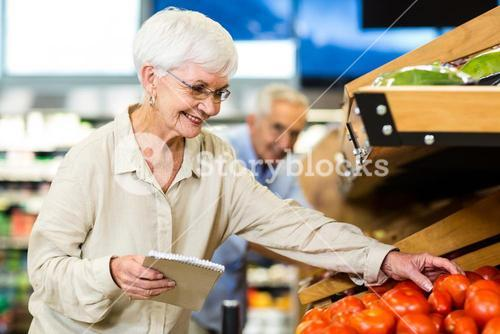 Smiling senior woman with list buying apple