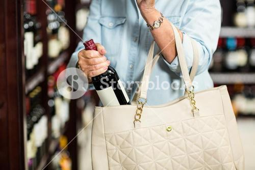 Mid section of senior woman putting wine bottle in the bag