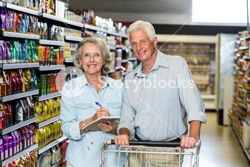Smiling senior couple with cart checking list