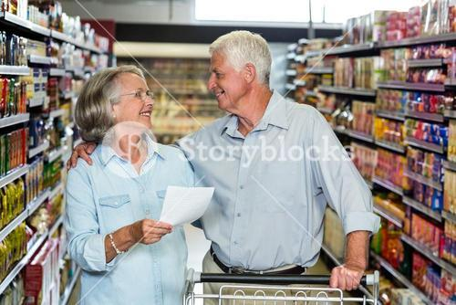 Smiling senior couple with cart and list