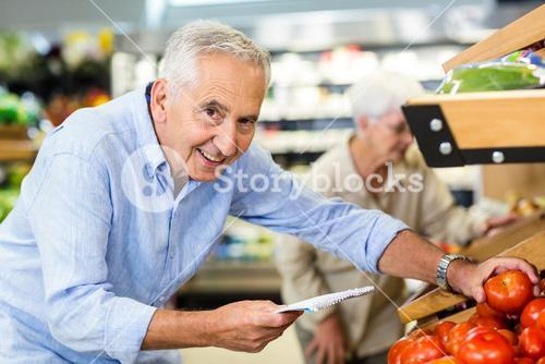 Smiling senior man with list buying apple