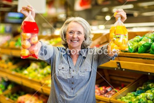 Senior happy woman holding bag of fruits