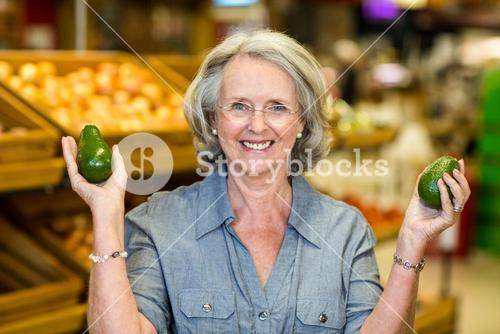 Senior woman holding two avocado