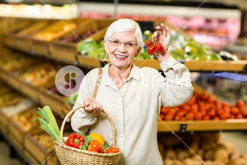 Senior woman holding basket and small tomatoes