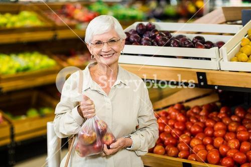 Senior woman holding bag with apple