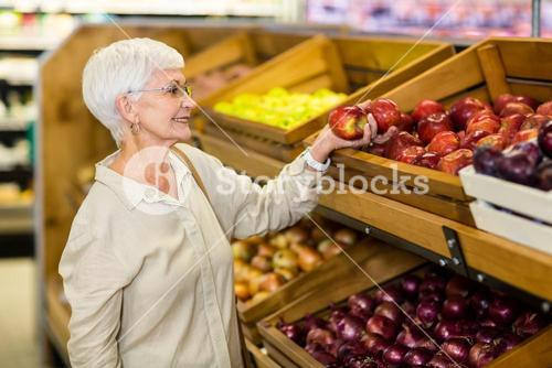 Senior woman picking out red apple