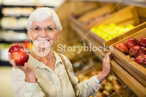 Senior woman picking out a red apple