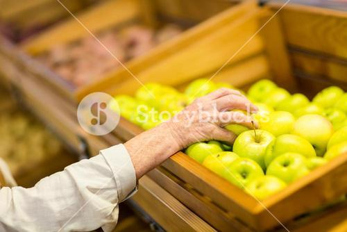 Senior woman picking out a green apple