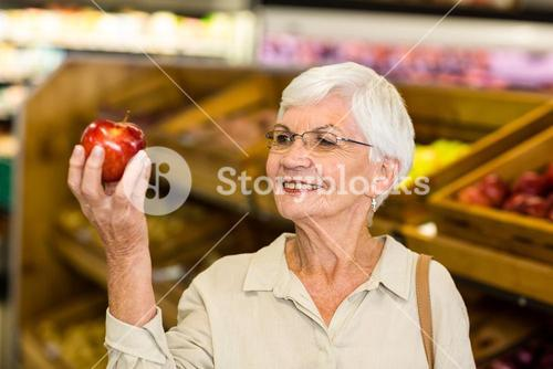Senior woman holding and watching a red apple