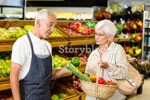 Senior customer and worker discussing vegetables