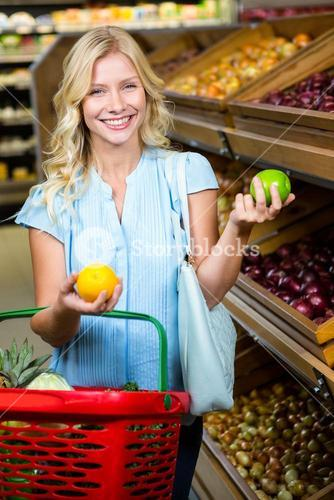Smiling woman with shopping basket holding apples