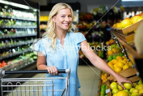 Smiling woman taking lemon