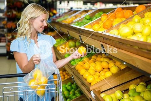 Smiling woman putting oranges in plastic bag