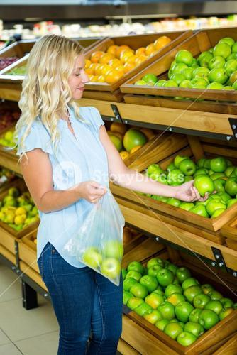 Smiling woman putting apples in plastic bag