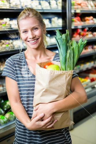 Beautiful woman standing with grocery bag