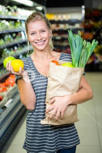 Beautiful woman standing with grocery bag and apples