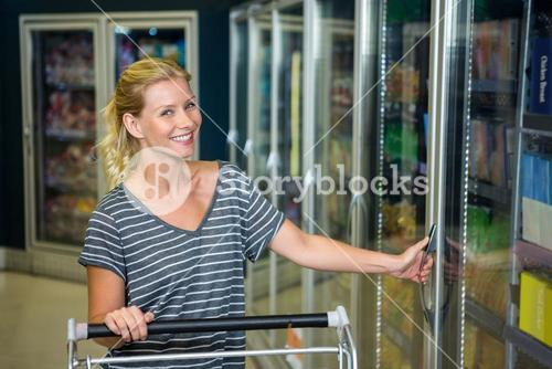 Smiling woman with cart opening fridge