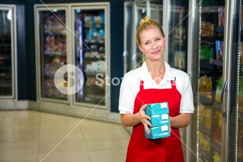 Smiling shop assistant holding products