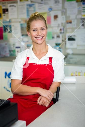 Smiling shop assistant with arms crossed