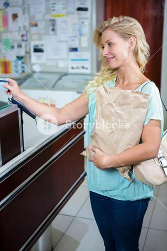 Smiling woman paying with credit card and holding grocery bag
