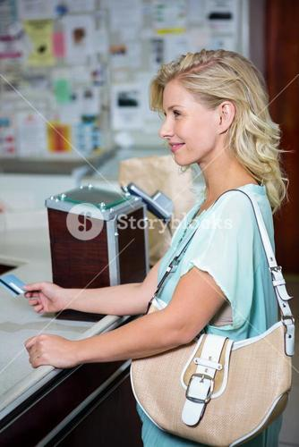 Smiling woman paying with credit card