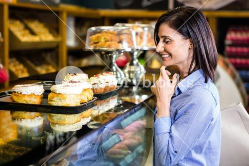 Pretty smiling woman choosing her dessert