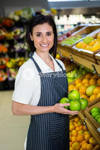 Portrait of a smiling worker taking a fruits