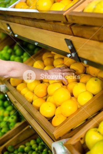 Close up view of a woman picking orange