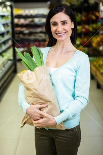 Pretty smiling woman holding grocery bag