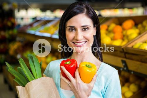 Smiling woman holding pepper and grocery bag