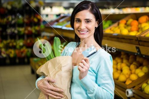 Smiling woman holding credit card and grocery bag