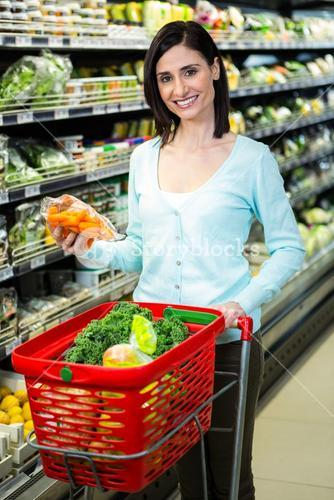 Smiling woman picking vegetables