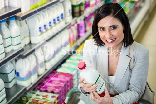 Smiling woman holding milk bottle