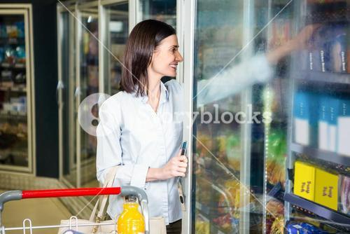 Smiling woman opening fridge